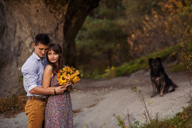 Sensual lovely couple in warm hugs on casual clothes staying near the rock with black dog