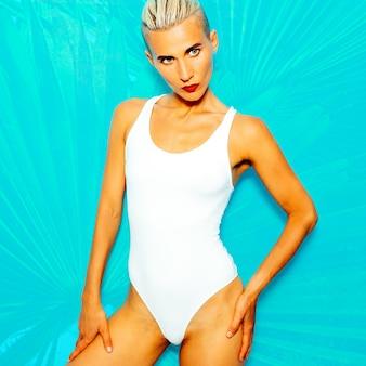 ファッショナブルな白い水着の官能的なモデル。ビーチファッションスタイル