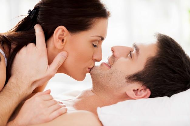 官能的な瞬間。女性が彼女のボーイフレンドのあごにキスしながらベッドに横たわっている美しい若い愛情のあるカップル