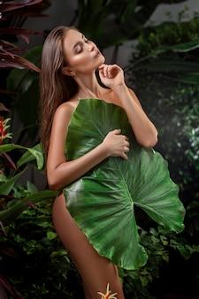 夏の熱帯の自然で官能的な裸の女性。大きな緑の植物を保持している滑らかな肌を持つ女性に合う