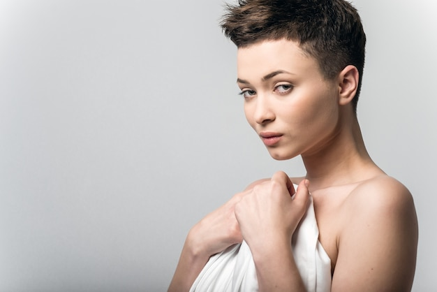 Sensual naked young adult caucasian woman, wrapped in a satin, silk sheet against grey background. high contrast