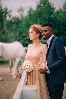 Sensual newlyweds stand on ranch surrounded by horses at sunset
