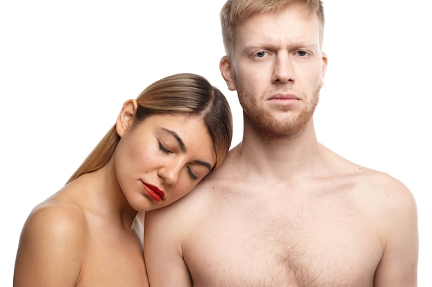 Sensual passionate adult couple posing topless: handsome unshaven male looking with serious expression while blonde woman keeping eyes closed and resting head on his shoulder