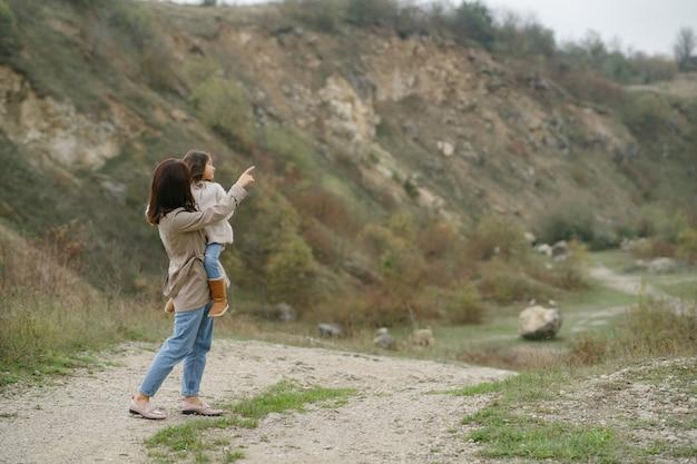 Sensual photo. cute little girl. people walks outside. woman in a brown coat.