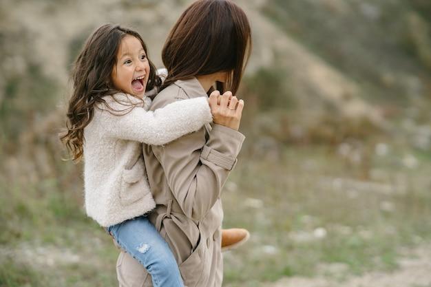 Foto sensuale. piccola ragazza carina. la gente cammina fuori. donna in un cappotto marrone.