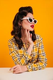 선글라스에 포즈 관능적 인 핀 업 아가씨. 노란색 체크 무늬 셔츠에 debonair 백인 여자의 스튜디오 샷.