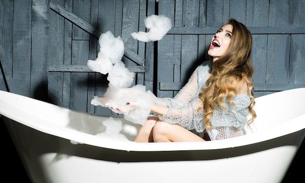 비누 거품을 가지고 노는 흰색 욕조에 관능적 인 장난 젊은 여자