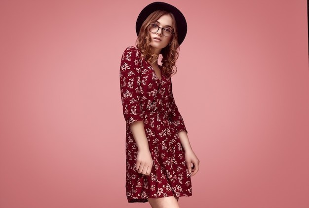 Sensual portrait of elegant glamor hipster girl in red fashion dress, black hat and glasses posing on colorful pink background in studio