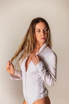 Чувственный портрет блондинки с большой грудью в расстегнутой белой рубашке на белом фоне. довольно молодая женщина в повседневной одежде позирует и смотрит в камеру и показывает эмоции. копировать пространство