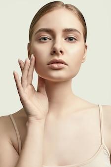 白でポーズをとってきれいな肌を持つ魅力的な女性モデルの官能的な肖像画