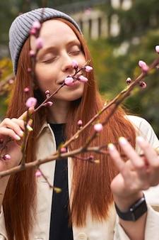 봄에 분홍색 꽃을 냄새 맡는 모자에 예쁜 빨간 머리 여자의 관능적 인 초상화 봄 공원 복사 공간 근접 촬영에 꽃과 피 나무에서 포즈 세련된 진정 여성 포즈