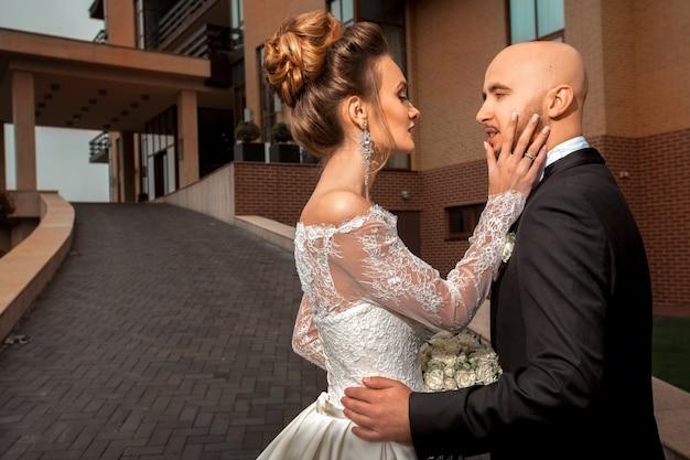 屋外でファッショナブルな結婚式のスーツを着た若い美しい夫婦の官能的な肖像画