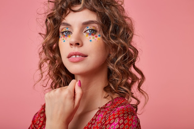 Чувственный портрет молодой девушки с кудрями, улыбающейся и держащей руку под лицом, изолированной, в полосатой розовой и оранжевой одежде