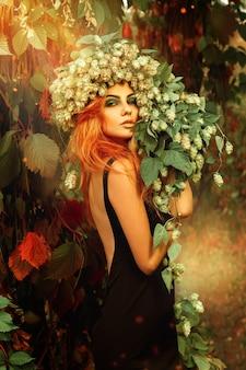 屋外の魔法の森で頭にホップの花輪を持つ若いredheair女性の官能的な肖像画
