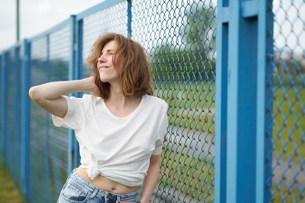 Sensual portrait of redhead skinny caucasian girl standing near fence