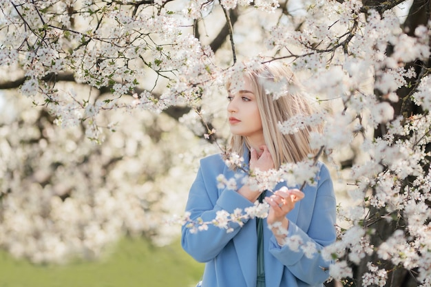 Sensual portrait of young blonde woman among blossoming apple tree