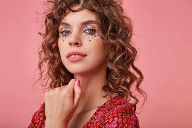 Sensuale ritratto di giovane donna con riccioli, sorridente e tenendo la mano sotto il viso, isolata, con indosso abiti a strisce rosa e arancioni