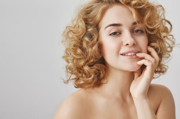 Чувственная симпатичная женщина с вьющимися волосами и обнаженными плечами, соблазнительно выглядит