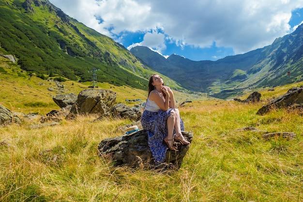 Чувственная красивая девушка в длинном синем белом платье сидит на скале на фоне высоких гор.