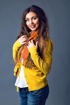 Чувственная довольно стильная брюнетка позирует, элегантная элегантная повседневная теплая уютная одежда, джинсовая ткань, кардиган и шарф, осенне-зимний модный стиль.