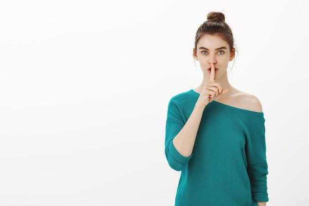 Sensuale donna graziosa che dice il segreto di bellezza, facendo il gesto di shh, zitto con il dito premuto sulle labbra