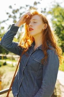 通りで太陽の光線でポーズをとるデニムシャツの官能的な赤い髪のモデル