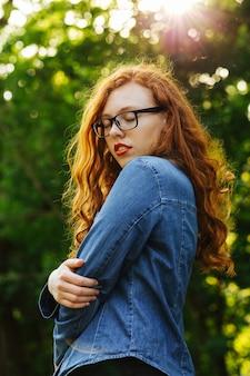 公園で太陽の光線でポーズをとってメガネで官能的な赤い髪の若い女性