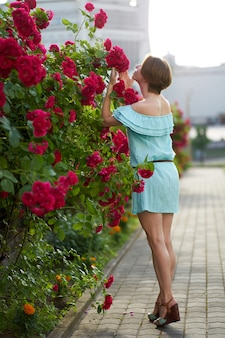 Sensual redhead girl wearing stylish blue light dress smelling blooming roses in the garden. outdoor.