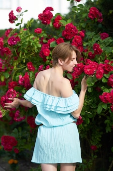 Sensual redhead girl wearing stylish blue light dress smelling blooming roses in the garden. view from back. outdoor.
