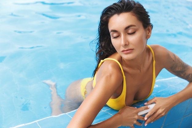 Sensual, relaxed tanned woman in a bikini, closed eyes, enjoying at the swimming pool.