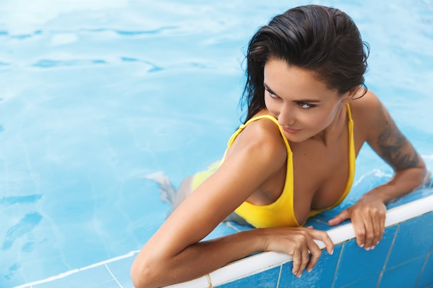 ビキニ姿の官能的でリラックスした日焼けした女性。脇を見て、プールで楽しんでいます。