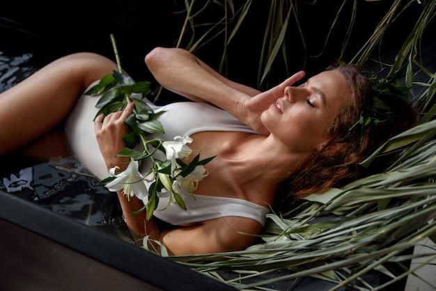 ユリの花を手にした白い水着の官能的な誘惑少女は、水と乾いた杖で満たされた黒いロフトスタイルのお風呂にあります。