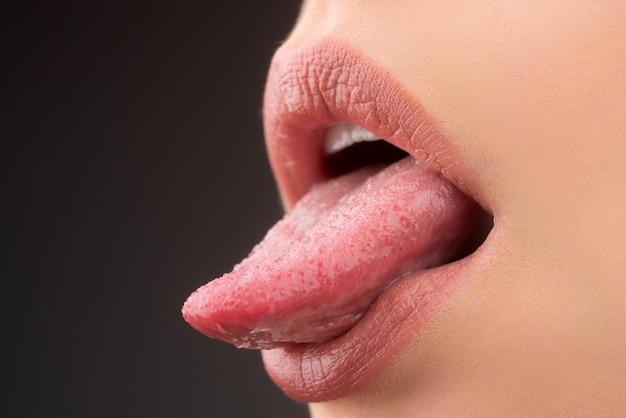 Sensual seductive mouth closeup. woman shows sexy tongue.