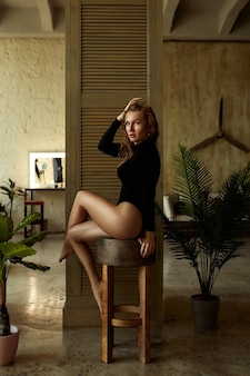 Sensual seductive young redhead woman with sexy legs in body posing in tropical interior.