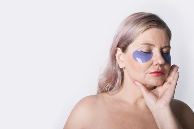 Чувственная старшая женщина с повязками на глазах позирует с закрытыми глазами и обнаженными плечами на белой стене, рекламируя что-то