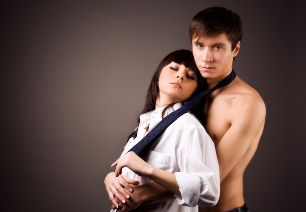 Sensual sexy couple a beautiful attractive woman and a slender sports man flirt and cuddle while looking at each other. the concept of passion and love. intimate concept
