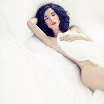 Чувственная сексуальная женщина спит в белой кровати