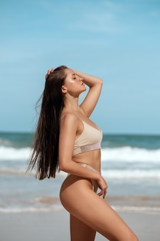 A sensual, slim lady  standing in the sea