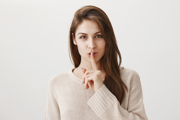 Sensual smiling woman shushing with finger pressed to lips, hiding secret