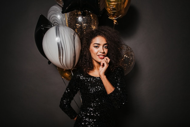 Sensual stylish woman holding bunch of party balloons