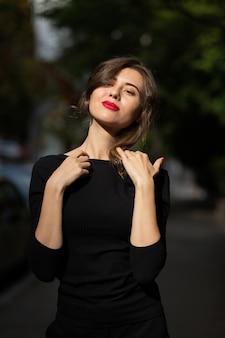 夏に通りを歩く古典的な黒い服を着た鮮やかなメイクで官能的なスタイリッシュな女性