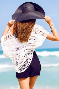 Sensual summer fashion portrait of elegant lady wearing hat and boho chic outfit posing at amazing tropical beach with blue clear sea. stay back looking to the ocean and enjoy her vacation