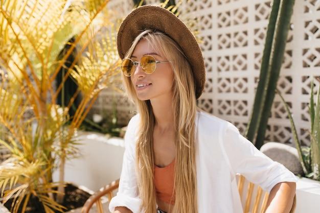 リゾートレストランでポーズをとっている間、目をそらしている官能的な日焼けした女の子。トレンディな茶色の帽子で美しいリラックスした女性の屋外ショット。