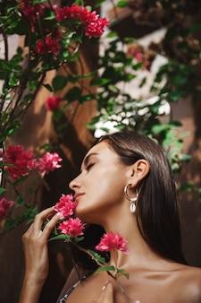 ビキニ姿の官能的な日焼けした女性、熱帯の花びらで顔に触れ、夏休みにリラックス。