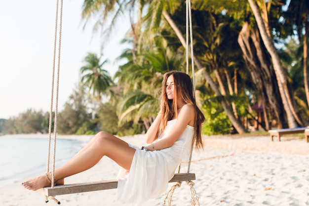 Sensual tender girl sitting on a swing wearing white dress. girl has her eyes closed. she has long dark hair. she has bracelets on her arm and leg. the swing is on the beach with green palms
