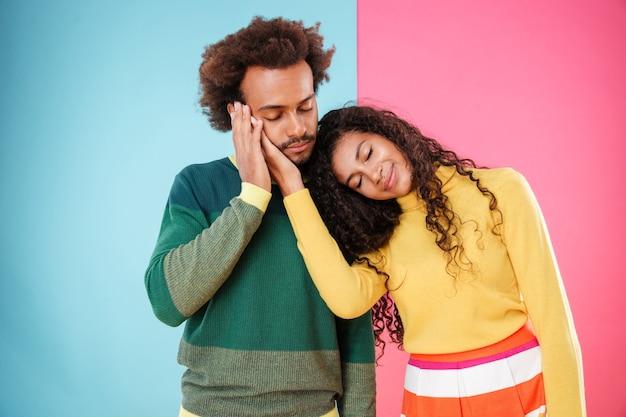 目を閉じて立っている官能的な疲れたアフリカ系アメリカ人の若いカップル
