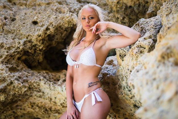 Modello sensuale bikini bagnato nelle onde del mare. donna spensierata che gode del bellissimo tramonto sulla spiaggia rocciosa