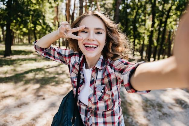 Sensuale ragazza bianca con zaino in posa con il segno di pace nella foresta. colpo esterno della splendida donna riccia che fa selfie nel parco e ridendo.