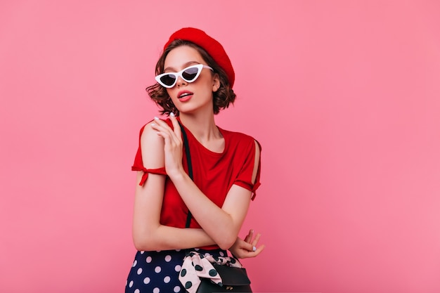 Sensual white lady in french hat posing. indoor photo of amazing curly girl in red beret enjoying.