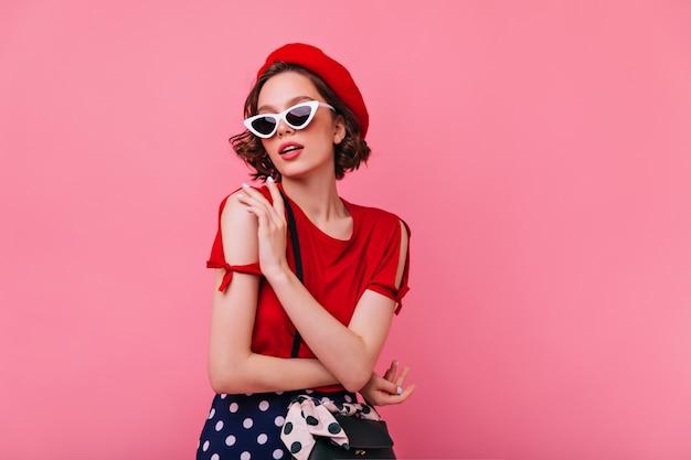 フランスの帽子のポーズで官能的な白人女性。赤いベレー帽を楽しんでいる素晴らしい巻き毛の女の子の屋内写真。